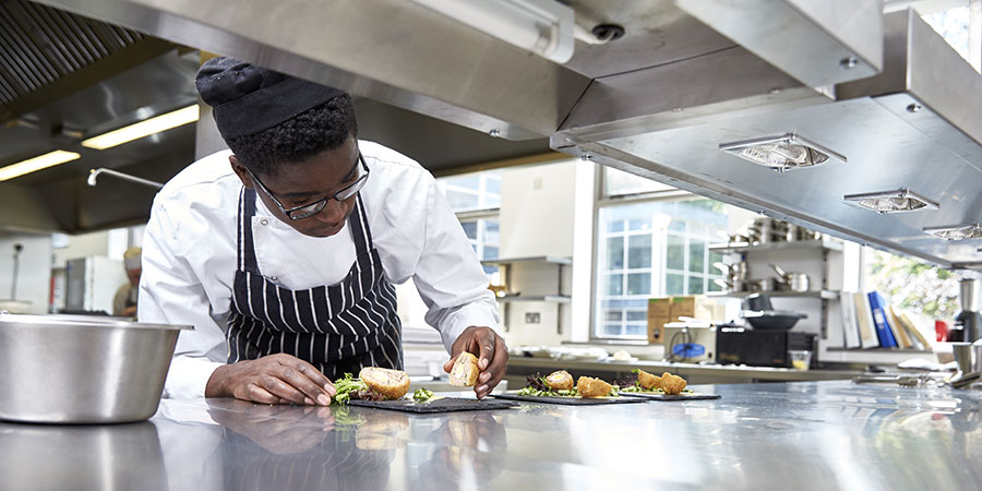 A student chef serving up food in the Mulberry Restaurant