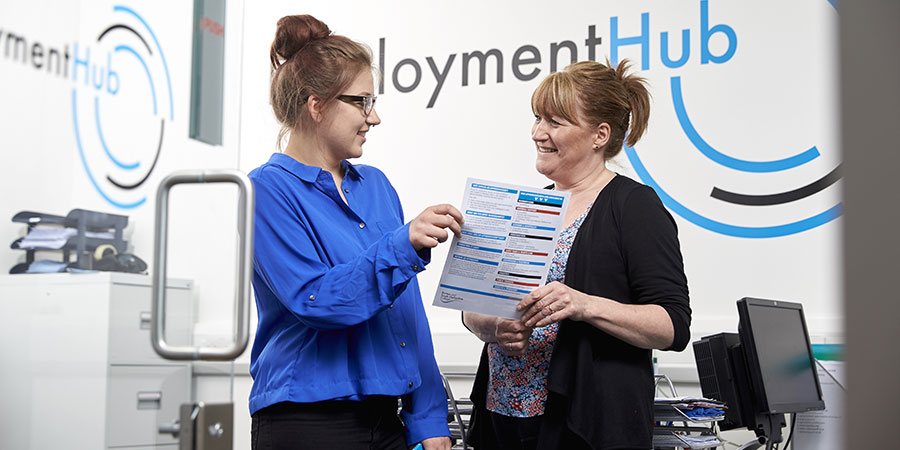 A student being handed a leaflet by a member of staff in the Employment Hub