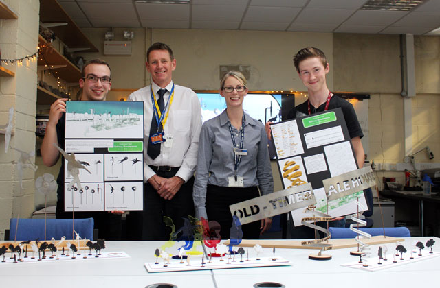 Students holding their designs with railway staff