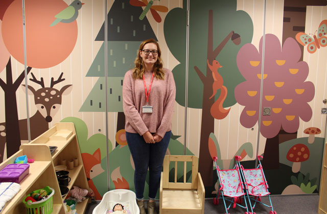 Holly Fyson with her woodland illustration on the wall of a college childcare classroom